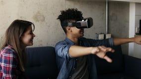 Νέος τύπος που δοκιμάζει το παιχνίδι εικονικής πραγματικότητας με τη φίλη του που βοηθά τον απόθεμα βίντεο