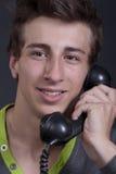 Νέος τύπος που μιλά στο παλαιά τηλέφωνο και το χαμόγελο Στοκ εικόνα με δικαίωμα ελεύθερης χρήσης