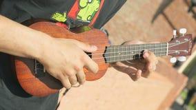 Νέος τύπος που παίζει μια ακουστική κιθάρα υπαίθρια απόθεμα βίντεο
