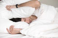 Νέος τύπος που προσπαθεί στον ύπνο, που καλύπτει το κεφάλι του με το μαξιλάρι στοκ εικόνες