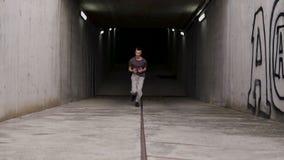 Νέος τύπος χούλιγκαν streetstyle που τρέχει έξω fron το χώρο στάθμευσης underearth από τη συγκεκριμένη μετάβαση φιλμ μικρού μήκους