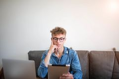 Νέος τύπος hipster στον επιτυχή συγγραφέα τρόπου ζωής γυαλιών που χρησιμοποιεί το μαξιλάρι αφής, που κάθεται στο σύγχρονο εσωτερι στοκ φωτογραφία με δικαίωμα ελεύθερης χρήσης