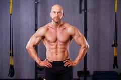 Νέος υγιής φαλακρός σχισμένος άνδρας με τους μεγάλους μυς που θέτουν στη γυμναστική στοκ φωτογραφία με δικαίωμα ελεύθερης χρήσης