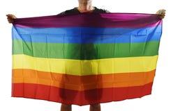 Νέος υπερήφανος ομοφυλόφιλος που διαδίδει την ευρεία μεγάλη ομοφυλοφιλική σημαία υπερηφάνειας με τη σκιά του πίσω από το ύφασμα Στοκ Φωτογραφία