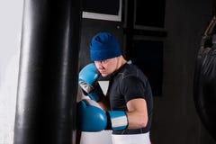 Νέος φίλαθλος αρσενικός μπόξερ στα εγκιβωτίζοντας γάντια που εκπαιδεύει με τον εγκιβωτισμό του PU Στοκ Φωτογραφίες