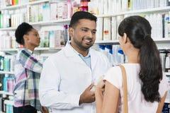 Νέος φαρμακοποιός που βοηθά το θηλυκό πελάτη στοκ εικόνα