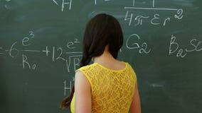 Νέος φοιτητής πανεπιστημίου που γράφει στον πίνακα κιμωλίας ή τον πίνακα κατά τη διάρκεια μιας κατηγορίας math φιλμ μικρού μήκους