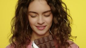 Νέος φραγμός σοκολάτας ανοίγματος γυναικών Πορτρέτο του ευτυχούς κοριτσιού που τρώει τη σοκολάτα απόθεμα βίντεο