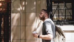 Νέος χαλαρωμένος ανεξάρτητος εργαζόμενος με το σακίδιο πλάτης που περπατά κατά μήκος του σκιερού κτηρίου οδών θερινών πόλεων με τ απόθεμα βίντεο