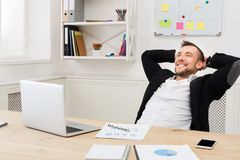 Νέος χαλαρωμένος επιχειρηματίας με το lap-top στο σύγχρονο άσπρο γραφείο Στοκ φωτογραφίες με δικαίωμα ελεύθερης χρήσης