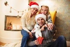 Νέος χαμογελώντας πατέρας στο καπέλο Santa ` s που δείχνει με το δάχτυλο σε σας, Στοκ εικόνα με δικαίωμα ελεύθερης χρήσης