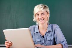 Νέος χαμογελώντας δάσκαλος με το lap-top στο σχολείο Στοκ εικόνα με δικαίωμα ελεύθερης χρήσης