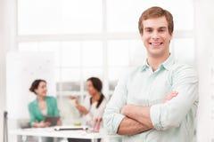 Νέος χαμογελώντας επιχειρηματίας που εξετάζει τη κάμερα Στοκ Εικόνες