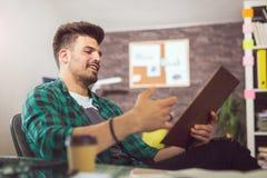 Νέος χαμογελώντας επιχειρηματίας που εργάζεται με τα έγγραφα στην αρχή Στοκ Φωτογραφίες