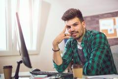 Νέος χαμογελώντας επιχειρηματίας που εργάζεται με τα έγγραφα στην αρχή Στοκ εικόνες με δικαίωμα ελεύθερης χρήσης