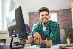Νέος χαμογελώντας επιχειρηματίας που εργάζεται με τα έγγραφα στην αρχή Στοκ φωτογραφία με δικαίωμα ελεύθερης χρήσης