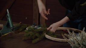 Νέος χαριτωμένος χαμογελώντας σχεδιαστής γυναικών που προετοιμάζει το αειθαλές στεφάνι δέντρων Χριστουγέννων Κατασκευαστής του ντ φιλμ μικρού μήκους