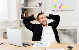 Νέος χαλαρωμένος επιχειρηματίας με το lap-top στο σύγχρονο άσπρο γραφείο Στοκ φωτογραφία με δικαίωμα ελεύθερης χρήσης