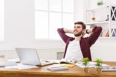 Νέος χαλαρωμένος επιχειρηματίας με το lap-top στο σύγχρονο άσπρο γραφείο Στοκ Φωτογραφία