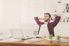 Νέος χαλαρωμένος επιχειρηματίας με το lap-top στο σύγχρονο άσπρο γραφείο Στοκ Εικόνες