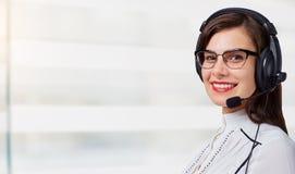 Νέος χειριστής τηλεφωνικών κέντρων γυναικών στην κάσκα στο υπόβαθρο γραφείων στοκ φωτογραφία