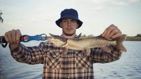 Νέος ψαράς που αλιεύει ενεργά στη λίμνη Το άτομο καταδεικνύει τους πιασμένους λούτσους στοκ εικόνα με δικαίωμα ελεύθερης χρήσης