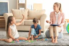 Νέος ψυχολόγος που συνεργάζεται με τα χαριτωμένα παιδιά στην αρχή στοκ εικόνες με δικαίωμα ελεύθερης χρήσης
