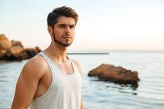 Νέος όμορφος αθλητής ατόμων που αναμένει στη δύσκολη παραλία Στοκ Εικόνες