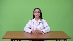 Νέος όμορφος ασιατικός γιατρός γυναικών που μιλά στη κάμερα φιλμ μικρού μήκους