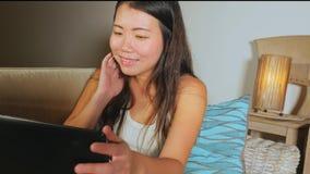 Νέος όμορφος ασιατικός κινεζικός σπουδαστών καναπές καναπέδων κοριτσιών ευτυχής και χαλαρωμένος στο σπίτι που χρησιμοποιεί Διαδίκ Στοκ εικόνες με δικαίωμα ελεύθερης χρήσης