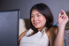 Νέος όμορφος ασιατικός κορεατικός σπουδαστών καναπές καναπέδων κοριτσιών ευτυχής και χαλαρωμένος στο σπίτι που χρησιμοποιεί Διαδί Στοκ Εικόνες