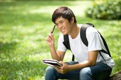 Νέος όμορφος ασιατικός σπουδαστής με τα βιβλία και χαμόγελο σε υπαίθριο Στοκ Φωτογραφίες