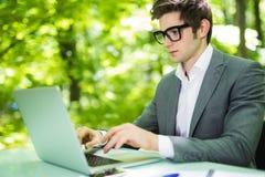 Νέος όμορφος διευθυντής που εργάζεται στο lap-top στον πίνακα γραφείων στο πράσινο πάρκο χρυσή ιδιοκτησία βασικών πλήκτρων επιχει Στοκ εικόνα με δικαίωμα ελεύθερης χρήσης