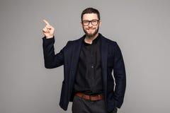 Νέος όμορφος επιχειρηματίας με την ακτινοβολία του χαμόγελου που δείχνει με το δάχτυλο Στοκ Εικόνες