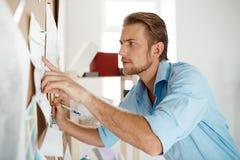 Νέος όμορφος επιχειρηματίας που δείχνει το δάχτυλο και που γράφει στο έγγραφο που καρφώνεται στο corkboard Υπόβαθρο γραφείων Στοκ φωτογραφία με δικαίωμα ελεύθερης χρήσης