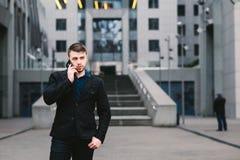 Νέος όμορφος επιχειρηματίας σε ένα σκοτεινό κοστούμι και ομιλία στο τηλέφωνο στο υπόβαθρο της σύγχρονης αρχιτεκτονικής Στοκ Εικόνες