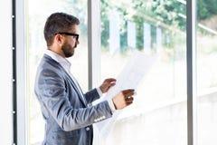 Νέος όμορφος επιχειρηματίας στο γραφείο του που μελετά τα σχέδια Στοκ φωτογραφία με δικαίωμα ελεύθερης χρήσης