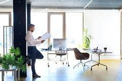Νέος όμορφος επιχειρηματίας στο γραφείο του που μελετά τα σχέδια Στοκ Εικόνες