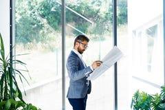 Νέος όμορφος επιχειρηματίας στο γραφείο του που μελετά τα σχέδια Στοκ Εικόνα