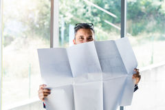 Νέος όμορφος επιχειρηματίας στο γραφείο του που μελετά τα σχέδια Στοκ Φωτογραφίες