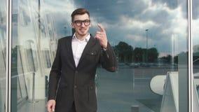 Νέος όμορφος επιχειρηματίας στο μαύρο κοστούμι που εξετάζει τη κάμερα και που δείχνει το δάχτυλο σε σας χειρονομία καμερών Ευτυχί απόθεμα βίντεο