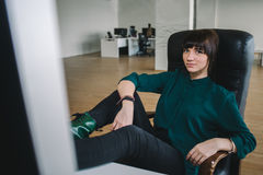 Νέος όμορφος εργαζόμενος σε μια σκοτεινή συνεδρίαση σακακιών στον εργασιακό χώρο κοντά στον υπολογιστή που ρίχνει τα πόδια του στ Στοκ Φωτογραφία