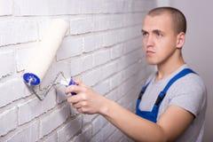 Νέος όμορφος ζωγράφος ατόμων στο workwear τουβλότοιχο ζωγραφικής με Στοκ εικόνες με δικαίωμα ελεύθερης χρήσης