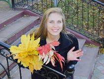 Νέος όμορφος η γυναίκα ο ξανθός με τα μπλε μάτια κρατά μια ανθοδέσμη των κίτρινων φύλλων φθινοπώρου διαθέσιμων Στοκ Φωτογραφία