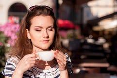 Νέος όμορφος καφές πρωινού κατανάλωσης γυναικών σε έναν υπαίθριο καφέ Στοκ φωτογραφία με δικαίωμα ελεύθερης χρήσης