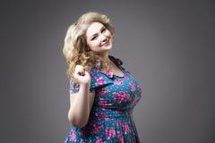 Νέος όμορφος ξανθός συν το πρότυπο μεγέθους στα dres, xxl πορτρέτο γυναικών στο γκρίζο υπόβαθρο στούντιο Στοκ φωτογραφία με δικαίωμα ελεύθερης χρήσης