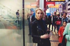 Νέος όμορφος ξανθός ταξιδεύει από τον καφέ κατανάλωσης λεωφόρων αγορών εργασίας στη συσσωρευμένη οδό Στοκ Εικόνα