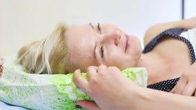 Νέος όμορφος ξανθός ύπνος γυναικών στο κρεβάτι της το πρωί απόθεμα βίντεο