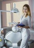 Νέος όμορφος οδοντίατρος γυναικών με ένα σημειωματάριο και μια μάνδρα ενάντια Στοκ εικόνα με δικαίωμα ελεύθερης χρήσης