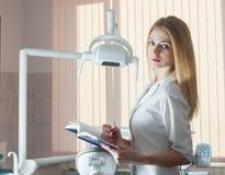 Νέος όμορφος οδοντίατρος γυναικών με ένα σημειωματάριο και μια μάνδρα ενάντια Στοκ Εικόνα